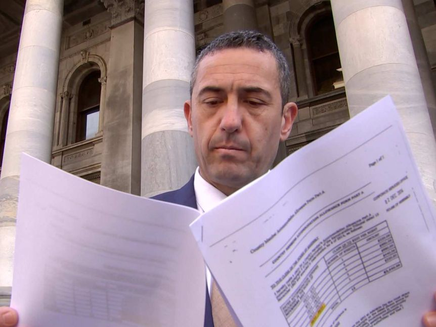 Tom Koutsantonis holds pieces of paper in front of his face in front of a building