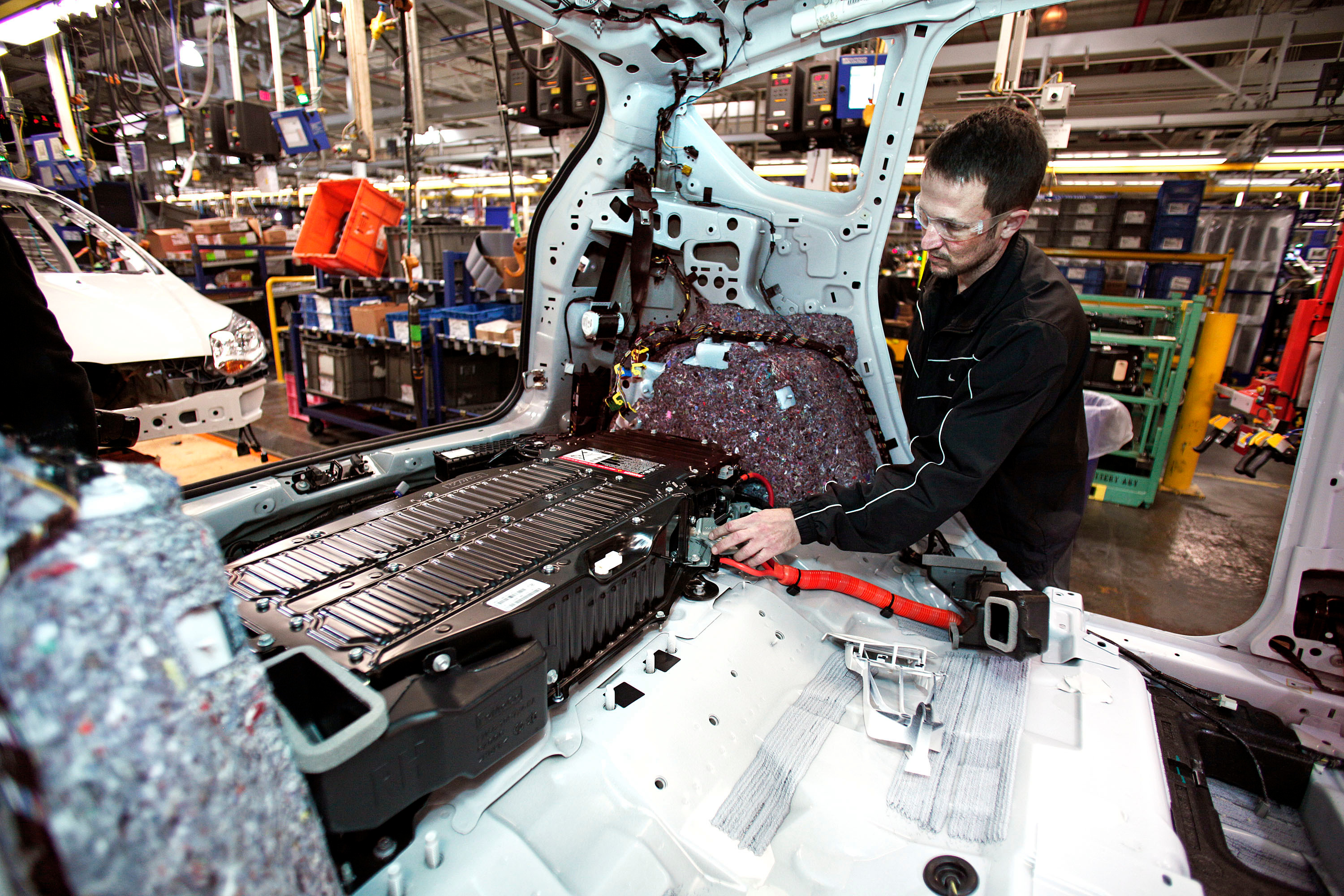 worker installs battery at Ford plant in Michigan