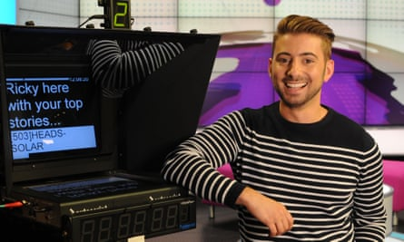 Ricky Boleto in a black and white striped t-shirt next to a screen in a TV studio
