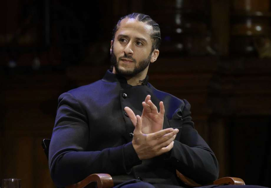 """FILE - NFL football quarterback Colin Kaepernick applauds during W.E.B. Du Bois Medal ceremonies at Harvard University in Cambridge, Mass. on Oct. 11, 2018. Kaepernick has been condemned by President Donald Trump and others on the right and had not played an NFL game since 2016, when he began kneeling during the National Anthem to protest """"a country that oppresses black people and people of color."""" But he has appeared in Nike advertisements, been honored by the ACLU and Amnesty International among other organizations and reached an agreement with the Walt Disney Co. for a docuseries about this life. Photo: Steven Senne, AP / Copyright 2018 The Associated Press. All rights reserved"""