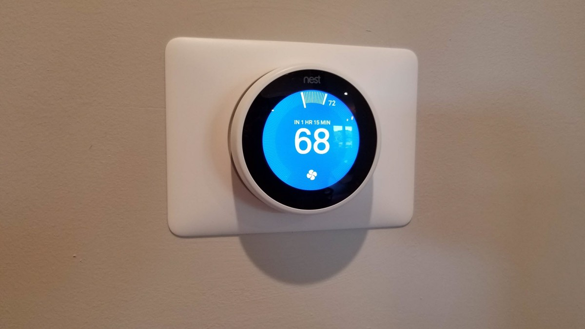 A Nest Thermostat on a white wall.