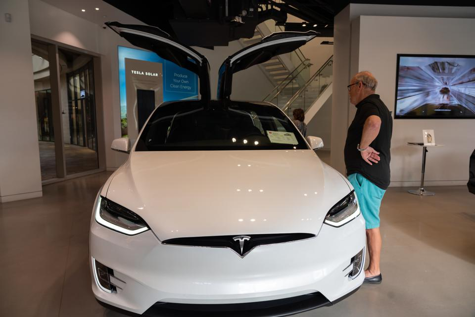 A customer looks at a Tesla Model X electric vehicle.