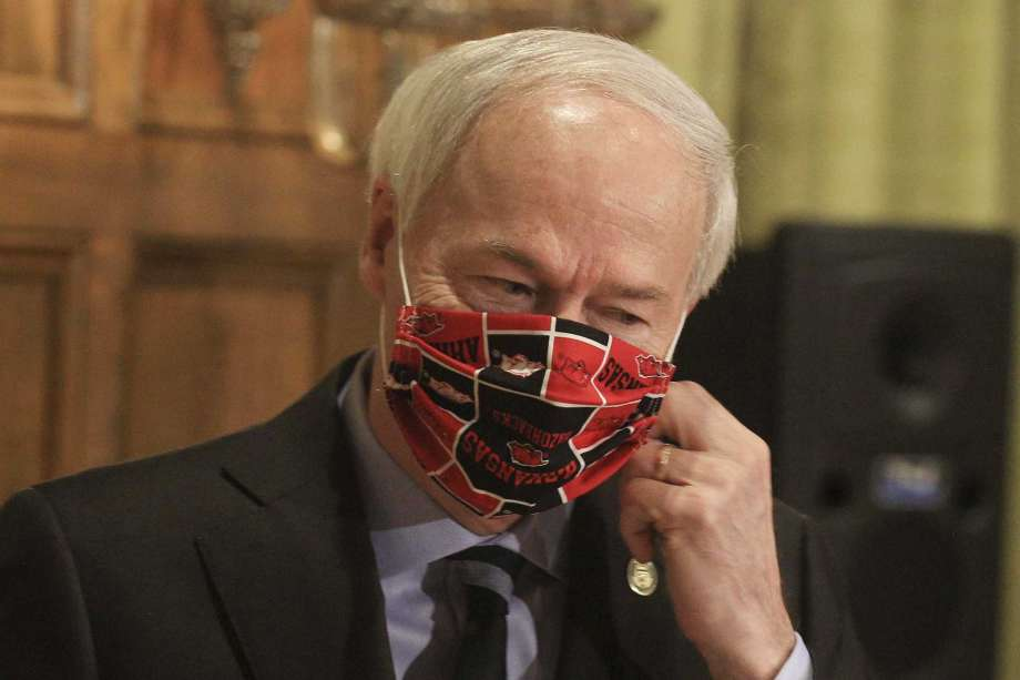 FILE - In this April 27, 2020 file photo, Gov. Asa Hutchinson takes off his Arkansas Razorbacks facemark as he arrives for the daily coronavirus briefing at the state Capitol in Little Rock. Hutchinson issued the order Thursday, July, 16, 2020, effective Monday, July 20, requiring people to wear masks in public throughout the state, which is dealing with a surge in coronavirus cases. The governor issued the order after weeks of resisting such a requirement. (Staton Breidenthal/Arkansas Democrat-Gazette via AP, File) Photo: Btaton Breidenthal, AP / The Arkansas Democrat-Gazette
