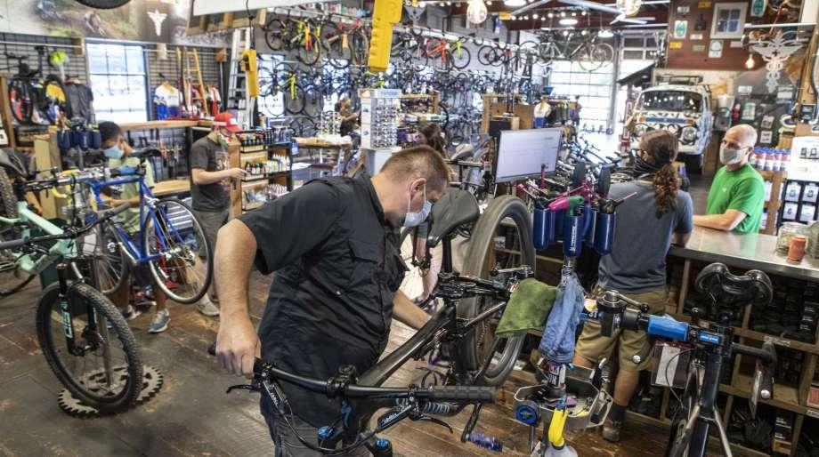 "Bike Surgeon's Mike ""Big Mike"" Eschmann works on a customer's bike in the service area in O'Fallon, Ill.   The Bike Surgeon has been busy since COVID-19 hit the region.  (Derik Holtmann/Belleville News-Democrat via AP) Photo: DERIK HOLTMANN, AP / Belleville News-Democrat"