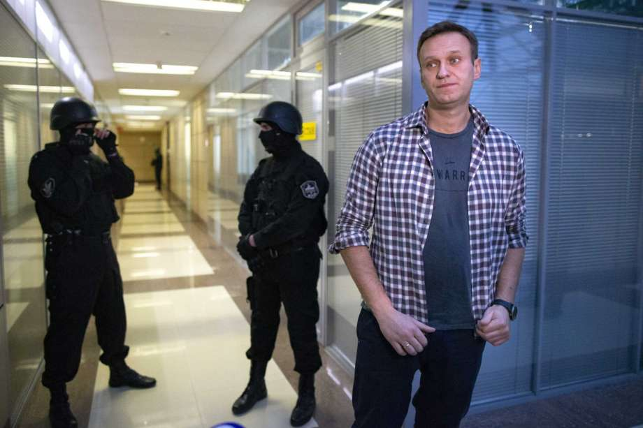 FILE - In this Thursday, Dec. 26, 2019 file, Russian opposition leader Alexei Navalny speaks to the media in front of security officers standing guard at the Foundation for Fighting Corruption office in Moscow, Russia. Navalny on Monday, July 20, 2020 announced the closure of his non-profit Anti-Corruption Foundation (FBK) over the court's order to pay massive damages in a controversial lawsuit, but said it would reopen under a new name. Photo: Alexander Zemlianichenko, AP / Copyright 2019 The Associated Press. All rights reserved.