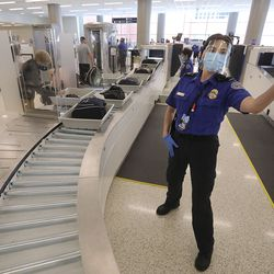 Transportation Security Administration officer Danielle Mercer directs travelers to vacant spots where they can load their belongings into bins on automated screening lanes at the new Salt Lake City International Airport on Tuesday, Sept. 22, 2020.