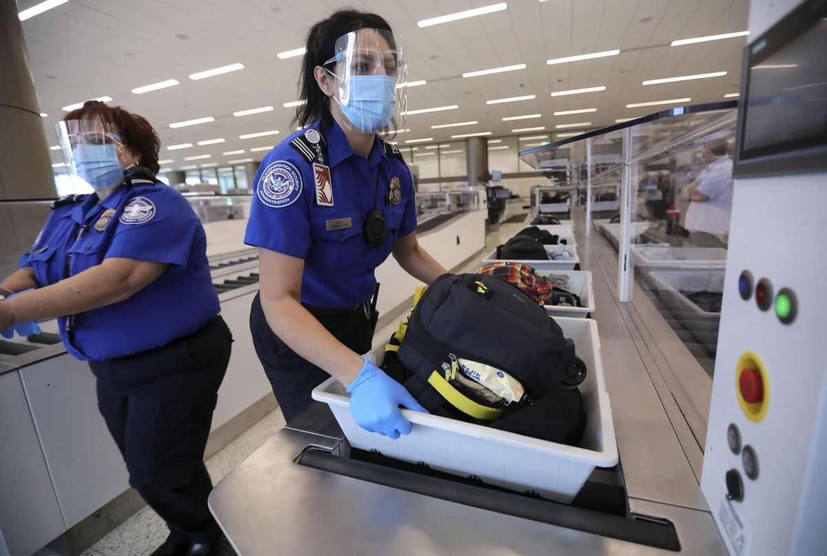 Anna Sosa, supervisory Transportation Security Administration officer, grabs a bin for additional screening at the TSA checkpoint at the new Salt Lake City International Airport in Tuesday, Sept. 22, 2020.