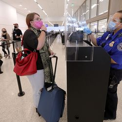 Transportation Security Administration officer Erica Burnella, right, checks Elaine York's ID at a TSA checkpoint at the new Salt Lake City International Airport on Tuesday, Sept. 22, 2020.