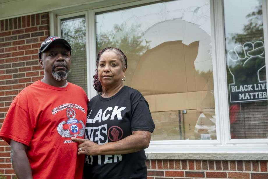 Eddie Hall Jr. and his wife Candace stand in front of the broken front window of their Warren, Mich., home, on Thursday, Sept. 10, 2020. An arrest has been made in connection with vandalism and shots fired into the couple's home. Warren Police Commissioner Bill Dwyer confirmed the arrest Tuesday night, Sept. 29 but didn't elaborate on charges or the person arrested. (David Guralnick/Detroit News via AP) Photo: David Guralnick, AP / Detroit News