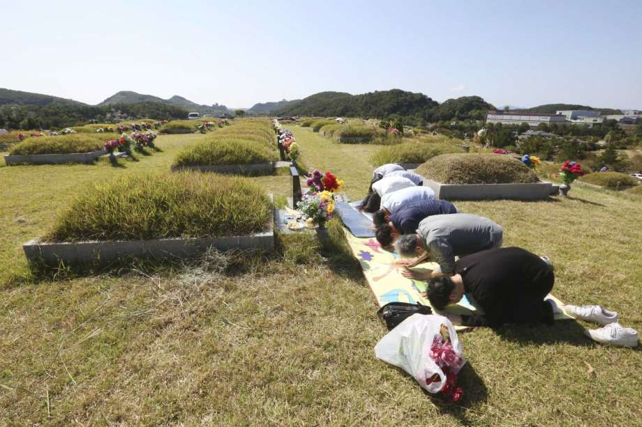 Family members bow to respect at their ancestral cemetery ahead of Chuseok holiday, the Korean version of Thanksgiving Day, at a cemetery in Paju, South Korea, Sunday, Sept. 27, 2020. South Korea's national cemeteries will be closed during the upcoming Chuseok holiday during the five-day holidays from Sept. 30 to Oct. 4 to prevent the spread of the coronavirus. Photo: Ahn Young-joon, AP / Copyright 2020 The Associated Press. All rights reserved.
