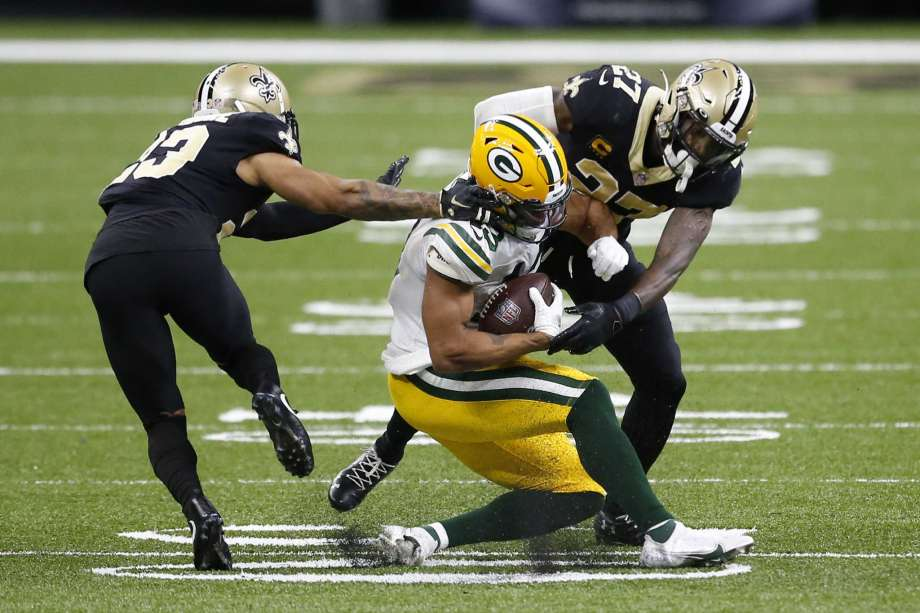 Green Bay Packers wide receiver Allen Lazard (13) is tackled by New Orleans Saints strong safety Malcolm Jenkins (27) and cornerback Marshon Lattimore in the second half of an NFL football game in New Orleans, Sunday, Sept. 27, 2020. Photo: Butch Dill, AP / Copyright 2020 The Associated Press. All rights reserved.