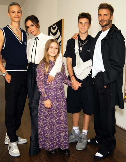 David Beckham, in his sliders and socks, with Victoria and their children Romeo (far left), Cruz and Harper Seven.