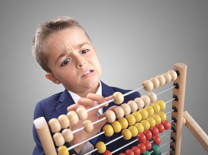 Puzzled boy using abacus