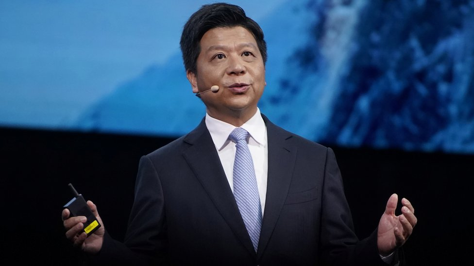 Guo Ping stands in front of a diffused blue photo on a conference stage, arms outstretched while speaking