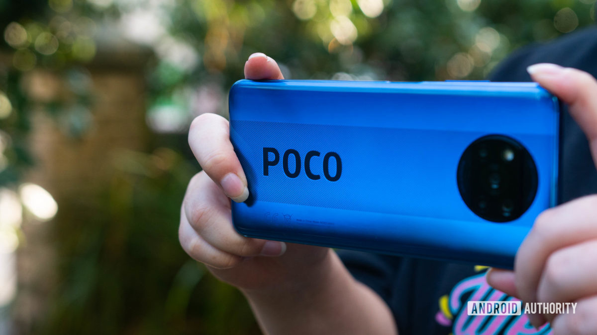 Xiaomi Poco X3 NFC held to take a photo showing off the rear side and POCO branding