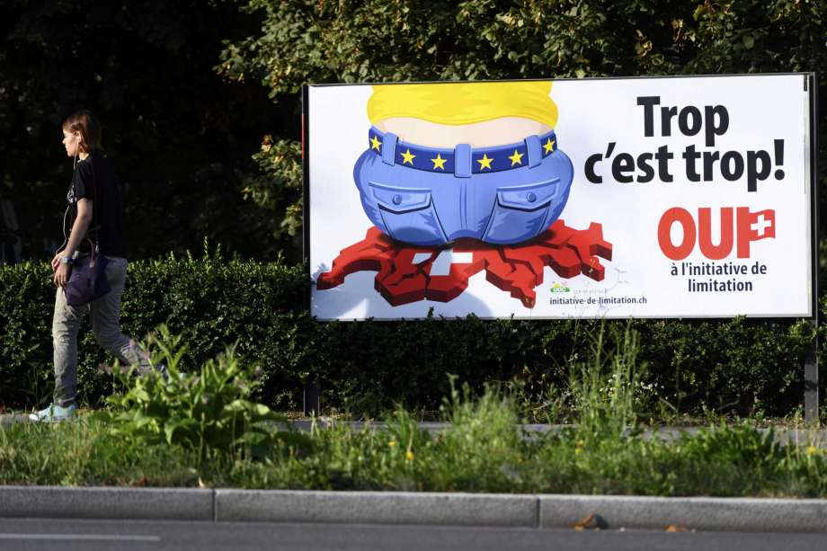 FILE - In this Aug. 27, 2020 file photo, a poster of the Swiss People's Party (SVP) for a moderate immigration initiative reading ''Enough is enough!'' is displayed in a street in Lausanne, Switzerland. The Swiss vote this weekend on whether to limit the number of European Union citizens who can live and work in Switzerland, a measure championed by a populist party that wants to make sure the Swiss get preferential access to jobs, social protections and benefits in the rich Alpine country. (Laurent Gillieron/Keystone via AP) Photo: LAURENT GILLIERON, AP / KEYSTONE