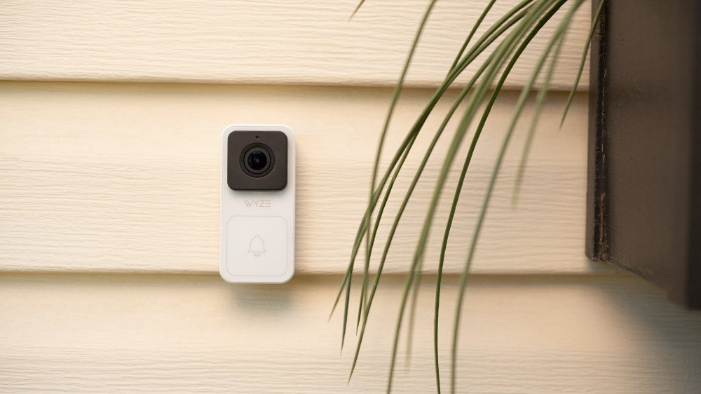 A Wyze video doorbell mounted to a white home.