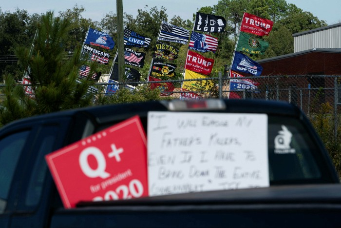 A QAnon sign is seen on a truck in the parking lot at a rally for President Donald Trump in Georgia this month. Critics blame Facebook for the proliferation of tkehe menacing, conspiracy theory group