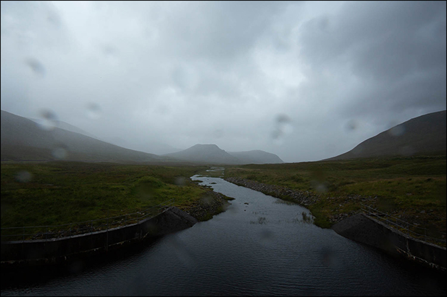 A rainy photo of a mountain and stream with droplets of water on the lens.