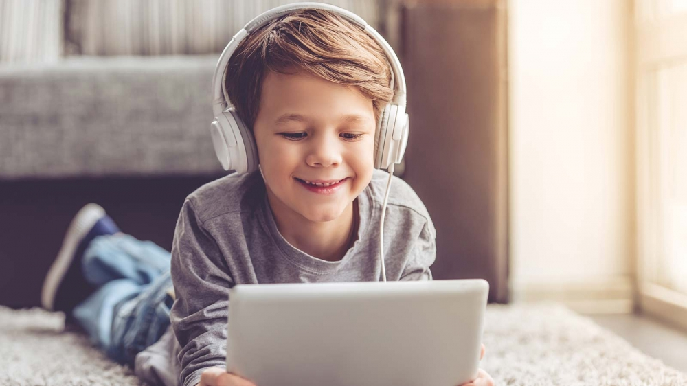A boy listening to headphones while using a tablet in a sunny living room.