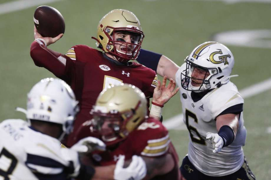 Boston College quarterback Phil Jurkovec, top left, passes under pressure from Georgia Tech linebacker David Curry (6) during the first half of an NCAA college football game, Saturday, Oct. 24, 2020, in Boston. Photo: Michael Dwyer, AP / Copyright 2020 The Associated Press. All rights reserved