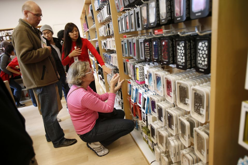A holiday shopper shops for iPhone accessories at the Apple Store during Black Friday in San Francisco, California, November 23, 2012. Black Friday, the day following the Thanksgiving Day holiday, has traditionally been the busiest shopping day in the United States. REUTERS/Stephen Lam (UNITED STATES - Tags: BUSINESS)