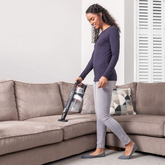 Woman cleaning the sofa with a Shark vacuum cleaner