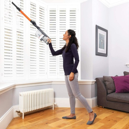 Woman cleaning the blinds with a Shark vacuum cleaner