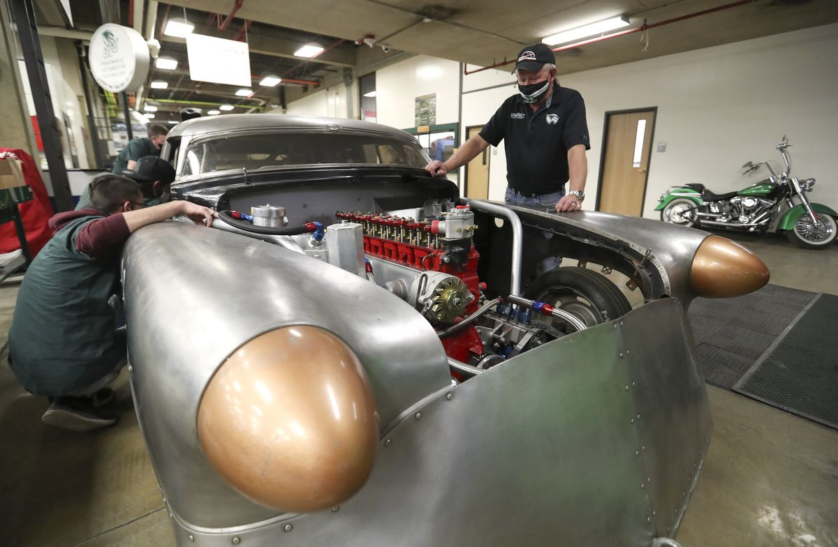 """Jeff Holm, UVU Transportation Technology professional in residence, right, and UVU automotive students work on """"Bombshell Betty,"""" the iconic 1952 Buick that broke six land speed world records at the Bonneville Speedway in Utah, at the Sparks Automotive building on the UVU campus in Orem on Wednesday, Nov. 18, 2020. The team has updated and reengineered the vehicle to break the 200 mph mark."""
