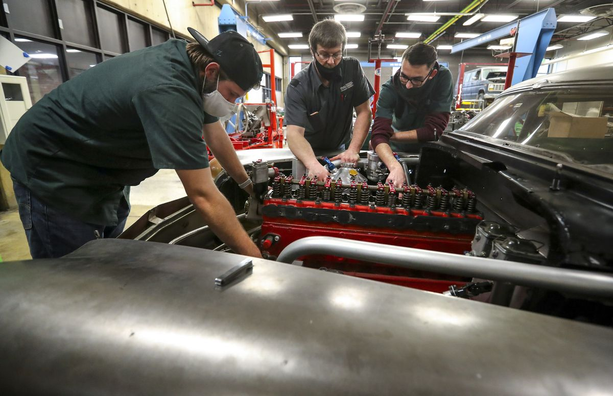 """Todd Low, center, UVU Automotive Department race team director, works with UVU automotive students Jordan Olsen, left, and Anderson Workman as they check the engine on """"Bombshell Betty,"""" the iconic 1952 Buick that broke six land speed world records at the Bonneville Speedway in Utah, at the Sparks Automotive building on the UVU campus in Orem on Wednesday, Nov. 18, 2020. The team has updated and reengineered the vehicle to break the 200 mph mark."""