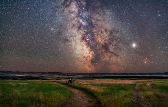 The core of the Milky Way in Sagittarius low in the south over the Frenchman River valley at Grasslands National Park, Saskatchewan. This is from the 76 Ranch Corral site. Grasslands is a Dark Sky Preserve. The frame takes in the openj star clusters M6 and M7 just above the horizon in Scorpius, on up through the Sagittarius Starcloud and galactic core, then up past the red nebulas M8 and M20, the Small Sagittarius Starcloud M24 flanked by the clusters M23 and M25, then the nebulas M17 and M16 at top in Serpens. The globular cluster M55 is visible at far left. Jupiter is bright at right above reddish Antares, Saturn is dimmer at left, to the left of the globular cluster M22. I shot this August 27, 2019. This is a stack of 5 x 3-minute tracked exposures for the sky (to avoid star trails) blended with a stack of 5 x 3-minute untracked exposures for the ground, all with the 35mm Canon lens at f/2.8 and filter-modified Canon 5D MkII camera at ISO 1600. The tracker was the Star Adventurer. (Photo by: Alan Dyer/VWPics/Universal Images Group via Getty Images)