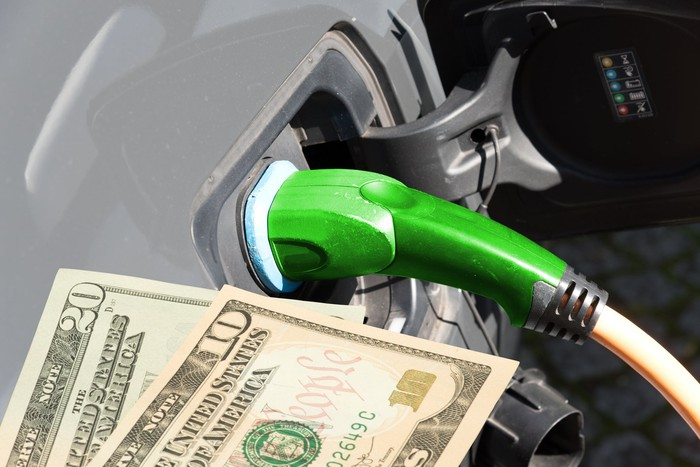 U.S. currency pictured along with an electric vehicle charging port