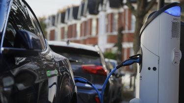 An electric car charges on a street charging port in London.