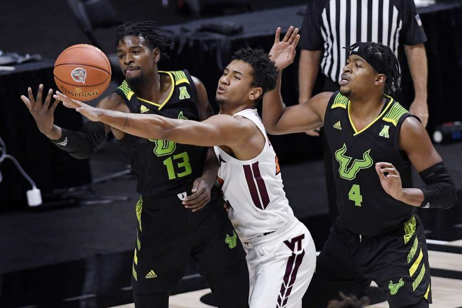 Virginia Tech's Keve Aluma, center, reaches between South Florida's Justin Brown, left, and South Florida's Michael Durr, right, for the ball in the first half of an NCAA college basketball game, Sunday, Nov. 29, 2020, in Uncasville, Conn. Photo: Jessica Hill, AP / Copyright 2020 The Associated Press. All rights reserved.