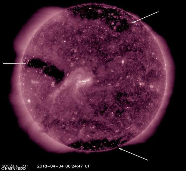 Strong solar winds emanating from three massive 'holes' on the surface of the sun have begun to bombard Earth, scientists say.Fast moving solar winds are created where the star¿s magnetic field opens up into space, captured as vast black regions in this satellite imagery