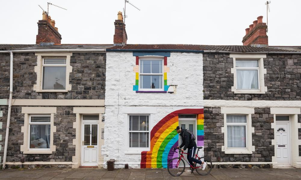 A man rides passed a terraced house painted with a rainbow in support of the NHS on Gwendoline Street in Cardiff, Wales, in April
