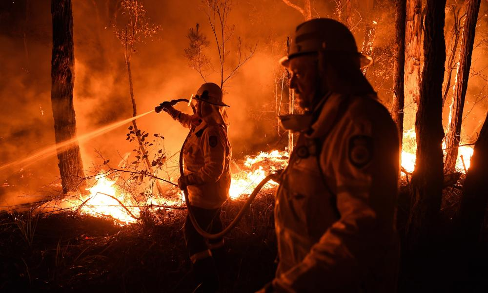 New South Wales firefighters work through the night to prevent a fire from crossing the Kings Highway between Nelligen and Batemans Bay in January