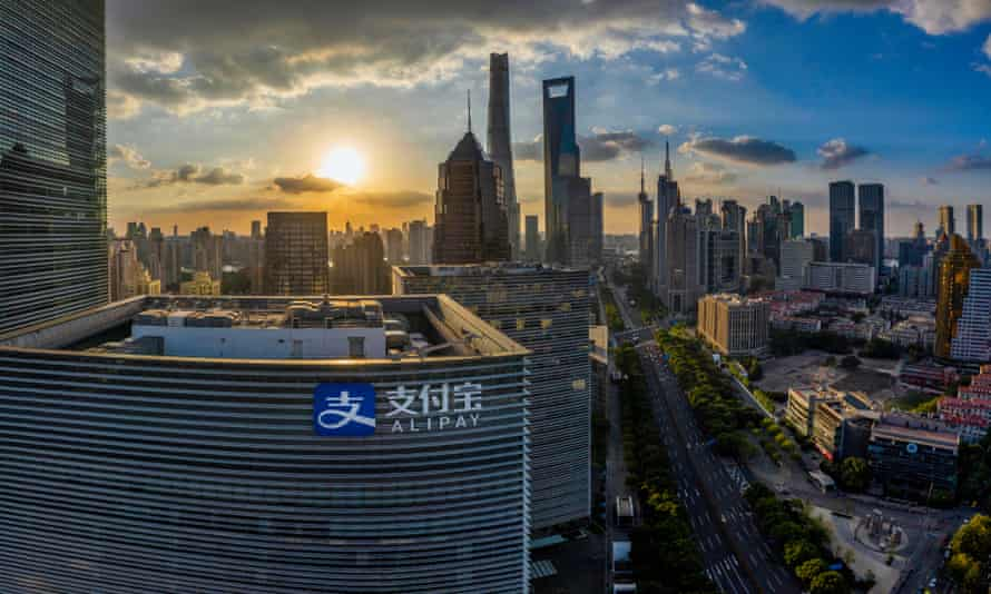 High-level view of skyscrapers in front of a  sunset in Shanghai. A building bearing the Alipay logo is closest to the camera