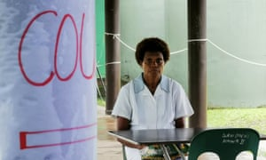 A nurse sits at a table set up as a Covid-19 screening station at Warangoin Clinic in East New Britain Province.