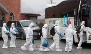Dressed in protective gear, students at the school in Daejeon where a COVID-19 cluster was identified get on a bus to head to a makeshift clinic.