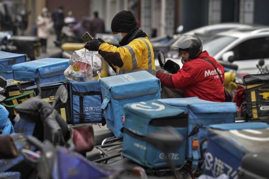 A food delivery worker wearing a face mask to help curb the spread of the coronavirus prepares to deliver foods for his customers outside a restaurant in Beijing on Thursday, Jan. 14, 2021. The e-commerce workers and delivery people who kept China fed during the pandemic, making their billionaire bosses even richer, are so unhappy with their pay and treatment that one just set himself on fire in protest. Photo: Andy Wong, AP / Copyright 2021 The Associated Press. All rights reserved