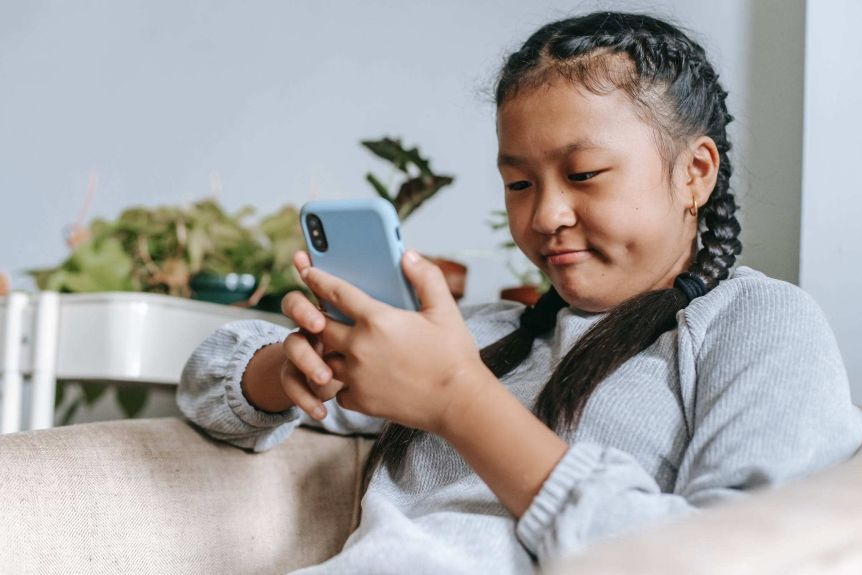 A young girl sits on the couch looking at her mobile phone.