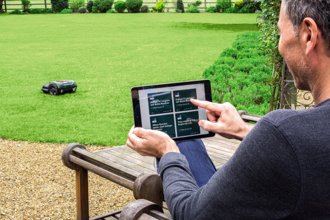 Man controlling a robot mower with a tablet