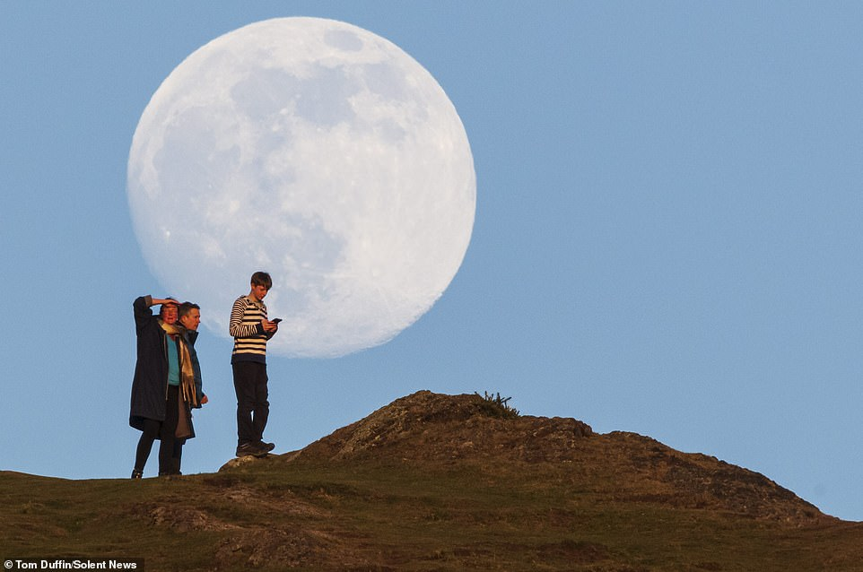 April's full moon, known as the pink moon, looms somewhat ominously behind Arthur's Seat in Edinburgh as a family enjoys a walk