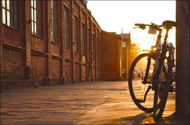 A bicycle parked on a city sidewalk at sunset.