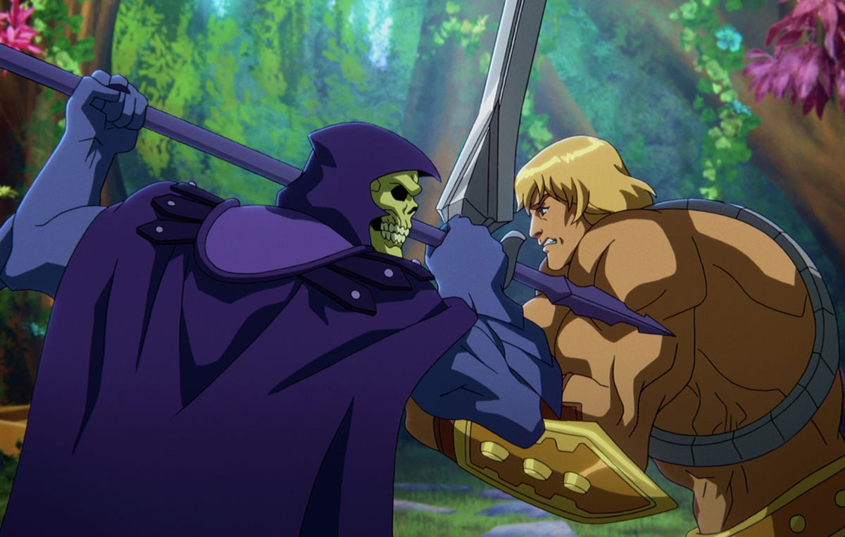 In a CG animated still from Masters of the Universe: Revelation, Skeletor (left), who wears a purple cloak and hood over his skull, grips his spear in a battle against He-Man (right), a strong shirtless blonde male with a golden armored belt and wrist plates holding a silver sword.