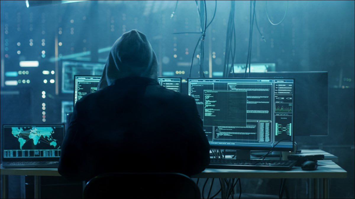 A hooded hacker sitting in front of computers.