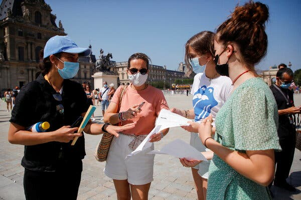 A security agent checked visitors' health passes in front of the entrance of the Louvre museum in Paris on Wednesday.