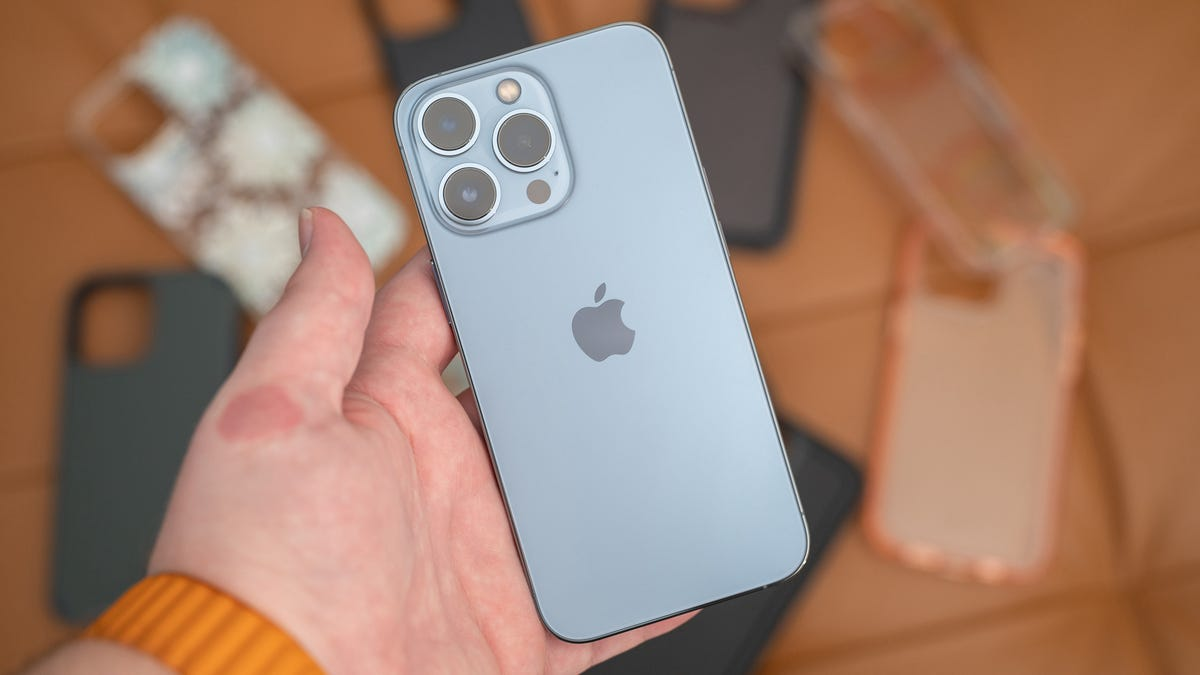 iPhone 13 Pro with cases in the background