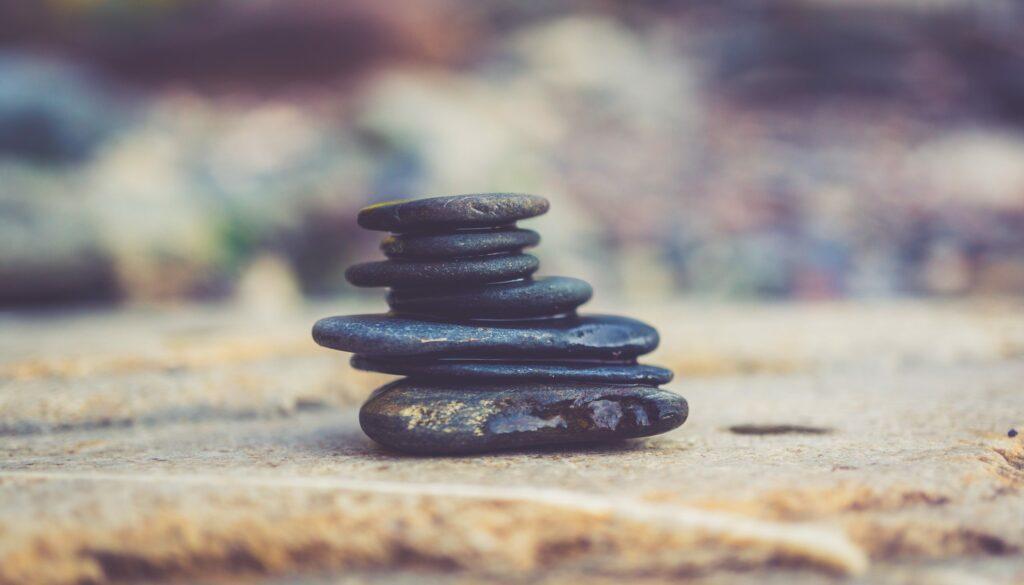 aufeinandergestapelte, flache, schwarze Steine mit verschwommenem Hintergrund